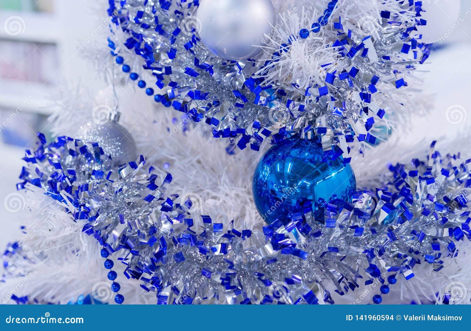 与蓝色和白色球和精采装饰的白色圣诞节快乐树