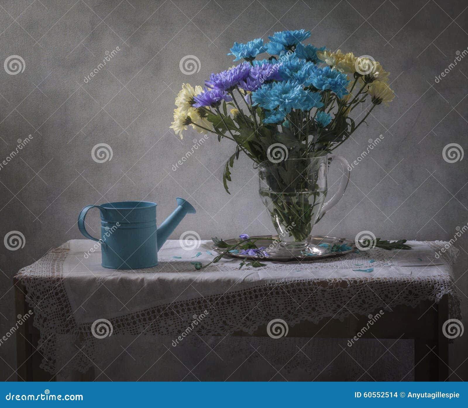 与蓝色喷壶的静物画和菊花花束图片