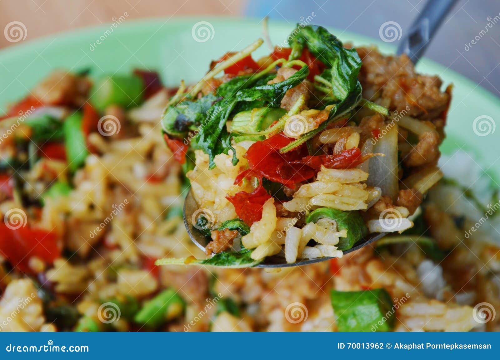 与蓬蒿叶子和米的混乱油煎的辣剁碎的猪肉在匙子