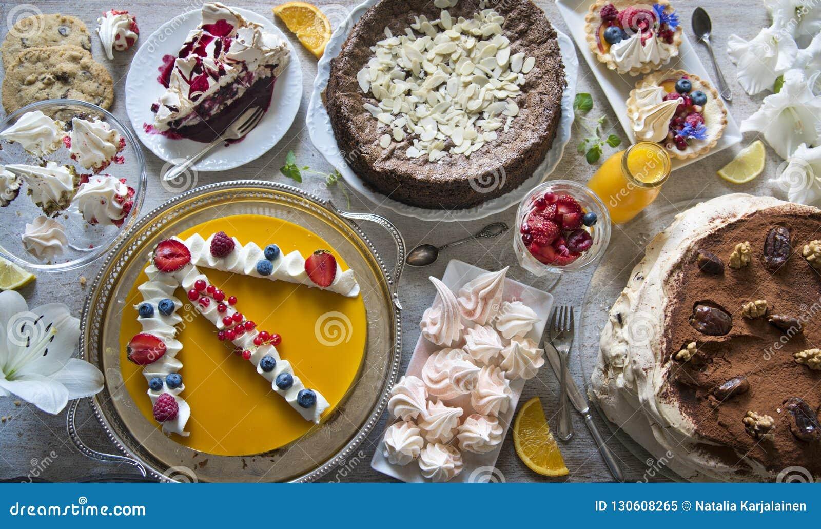 与蛋糕、杯形蛋糕、曲奇饼、cakepops、点心、果子、花和橙汁过去装载的表