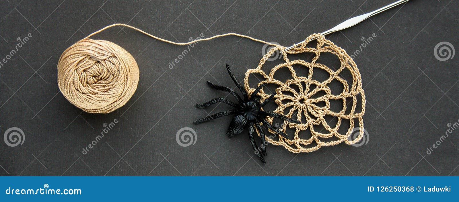 与螺纹黑橡胶蜘蛛、钩针编织和棉纱品球的钩针编织的蜘蛛网在黑纸背景的 黑暗的万圣夜octob