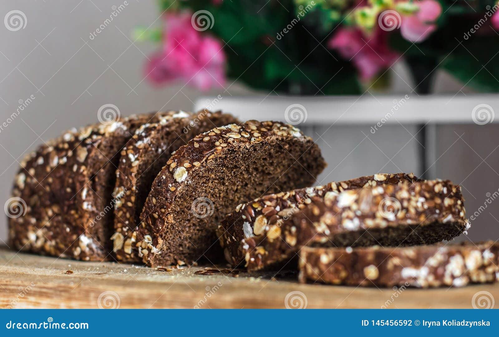 与被切的种子的黑麦面包 在老木板条的切的黑面包在花装饰的背景