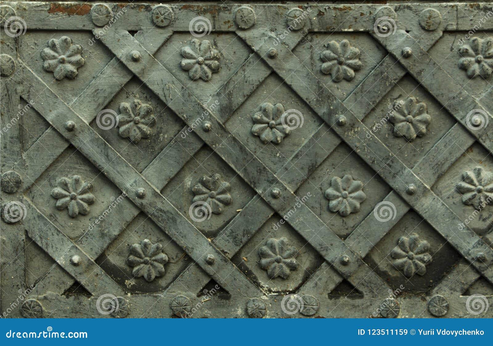 与装饰覆盖物的古老伪造的金属纹理 门,门,快门 中世纪灰色门的细节与金属decoratio的