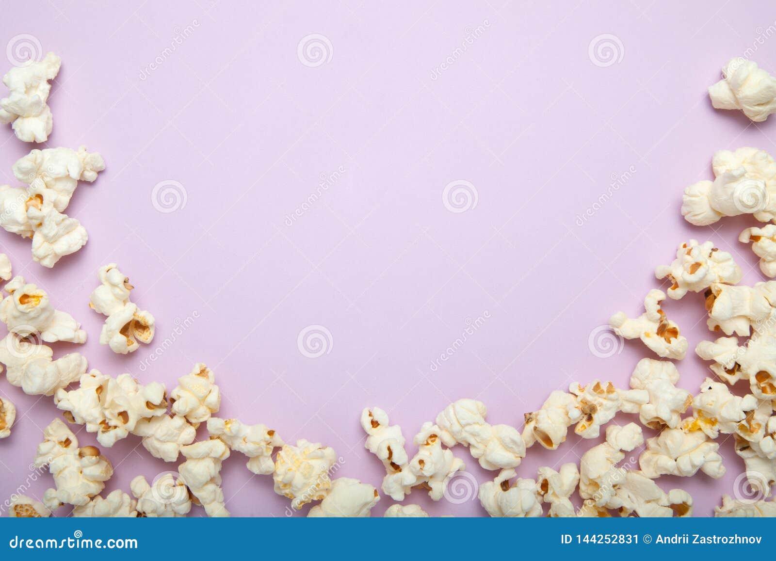 与许多的戏院概念在桃红色背景的蓬松玉米花与拷贝空间