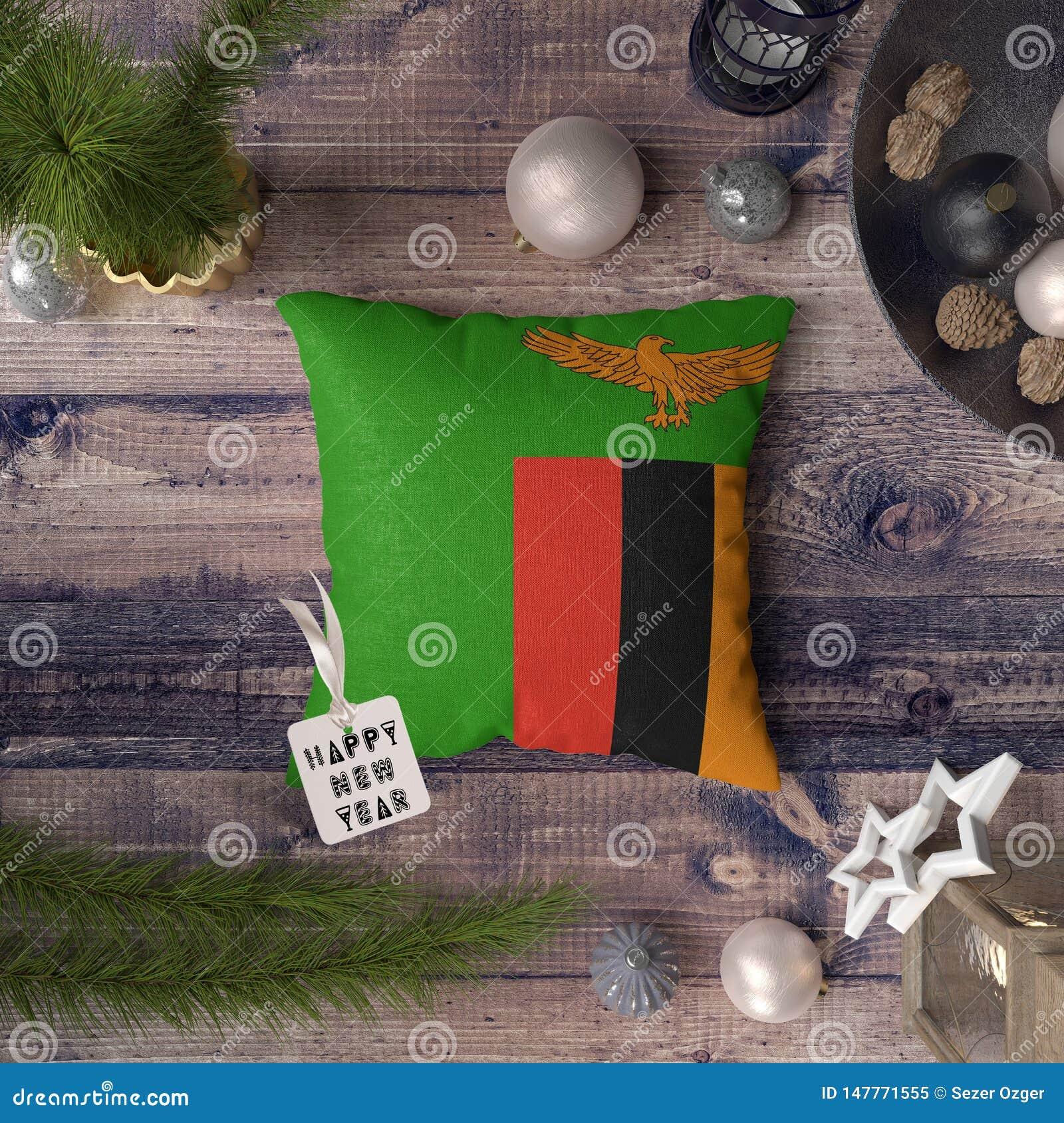 与赞比亚旗子的新年快乐标记在枕头 在木桌上的圣诞装饰概念与可爱的对象
