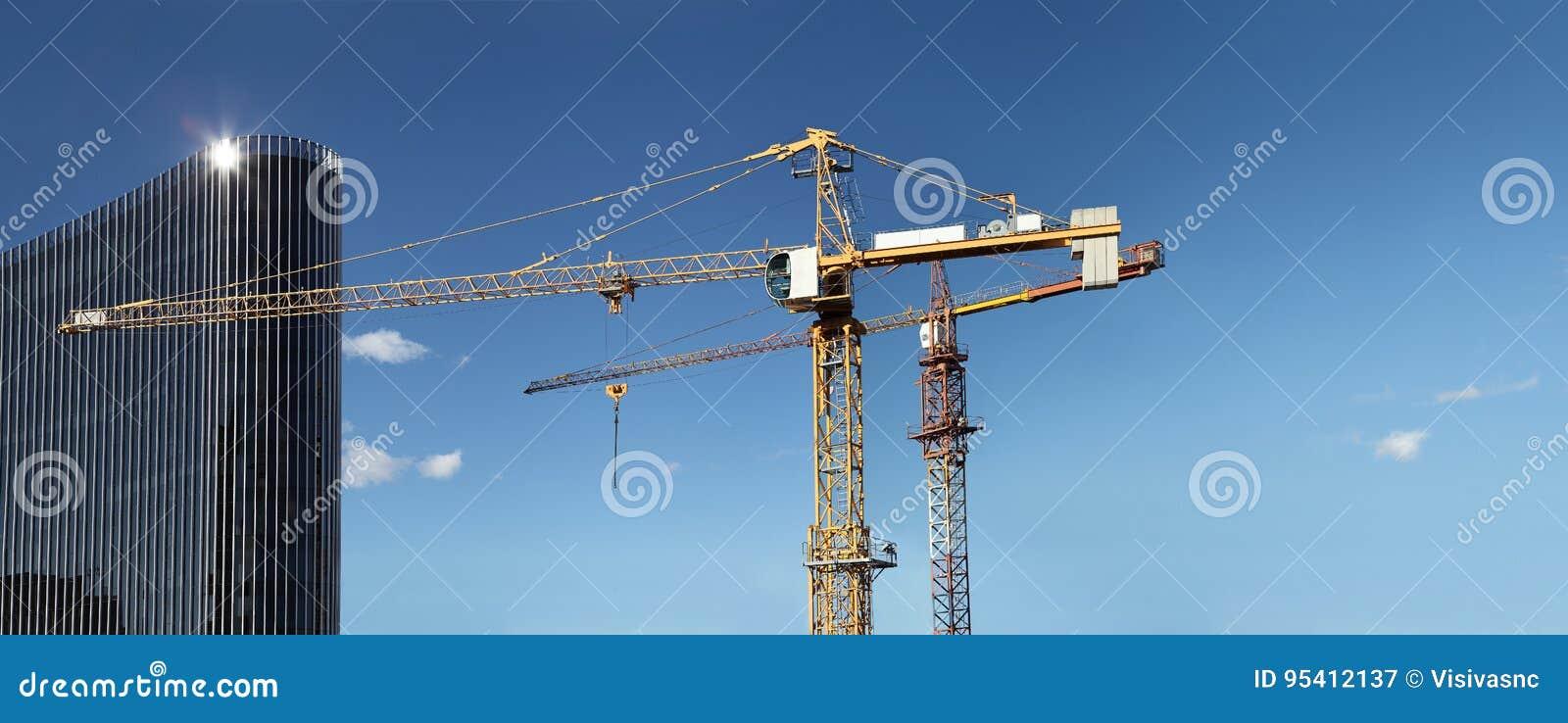 与起重机和玻璃摩天大楼的建设中站点大厦