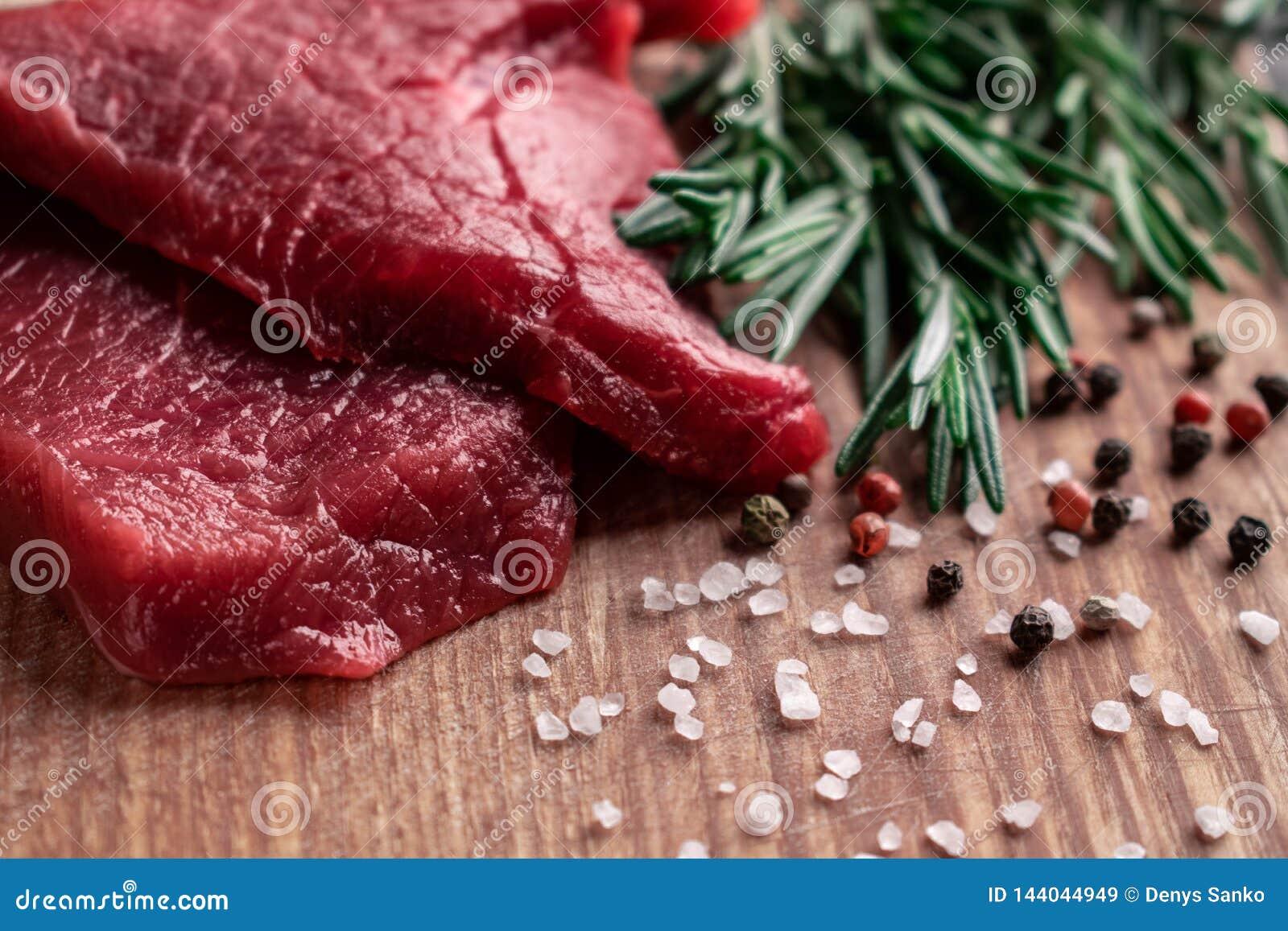 与迷迭香黑色、红辣椒和粗糙的海盐的未加工的牛排