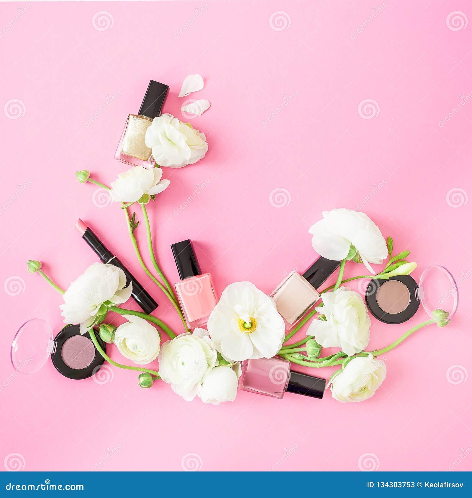 与郁金香花和化妆用品的构成在桃红色背景 顶视图 平的位置女性书桌