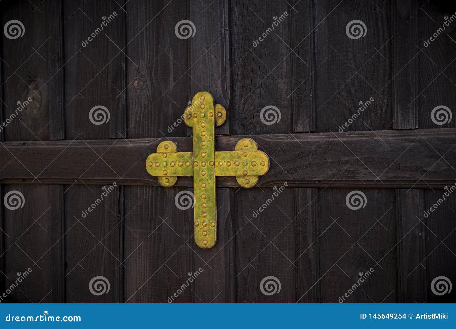 与金属金黄色的基督徒十字架的葡萄酒木门在基督教会里