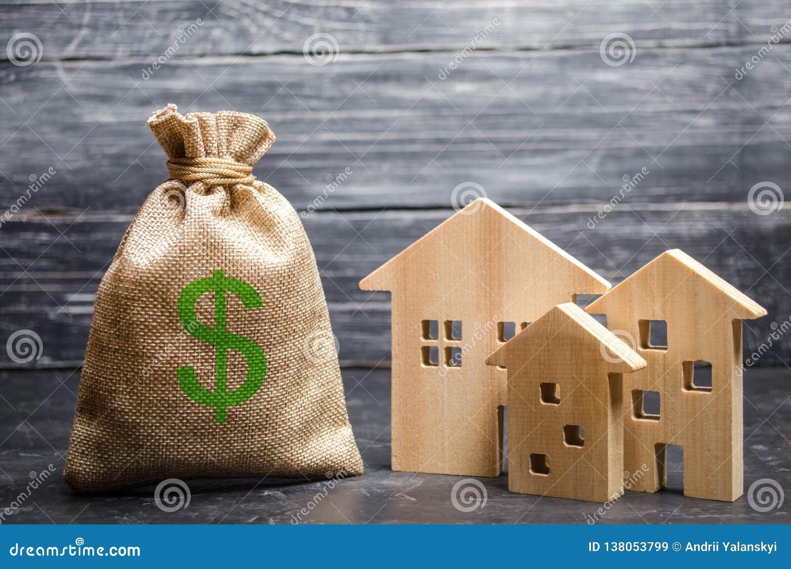 与金钱和三个房子的一个袋子 不动产承购和投资的概念 付得起的便宜的贷款,抵押 税务