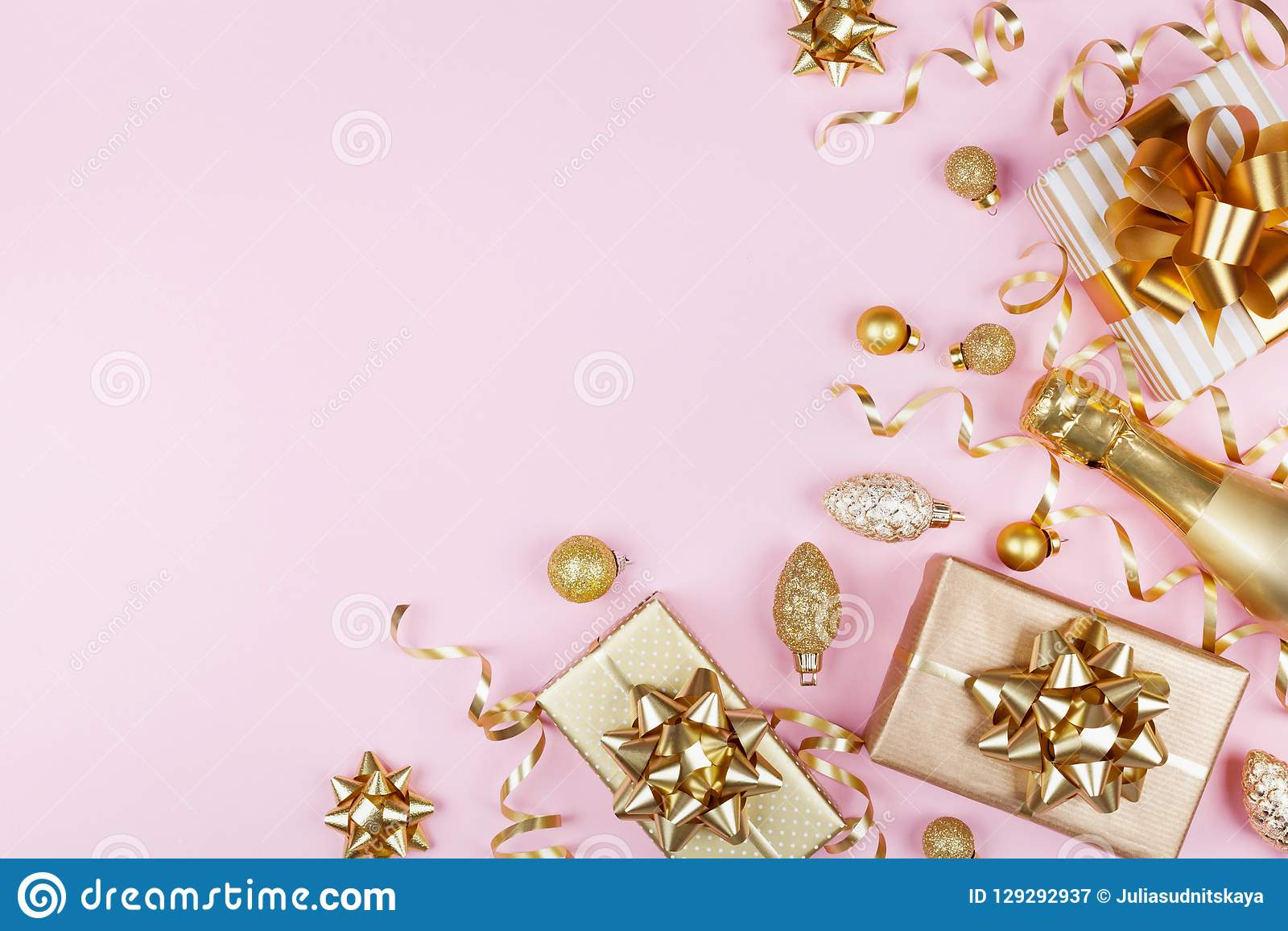 与金黄礼物的圣诞节背景或当前箱子、香槟和假日装饰在桃红色淡色台式视图 平的位置