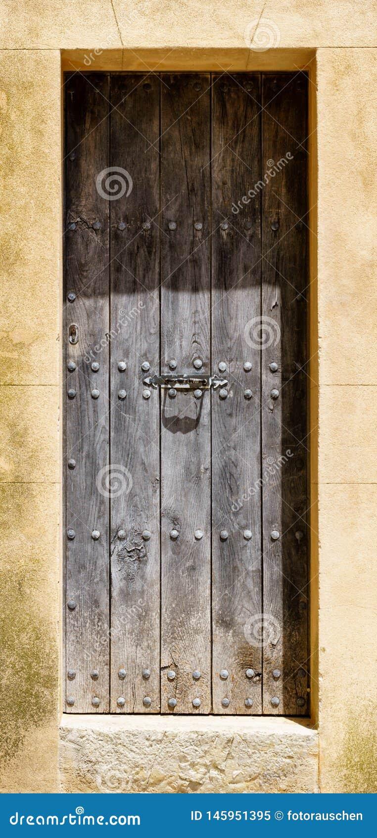 与铆钉的巨型的木门在这是被风化的石头框架