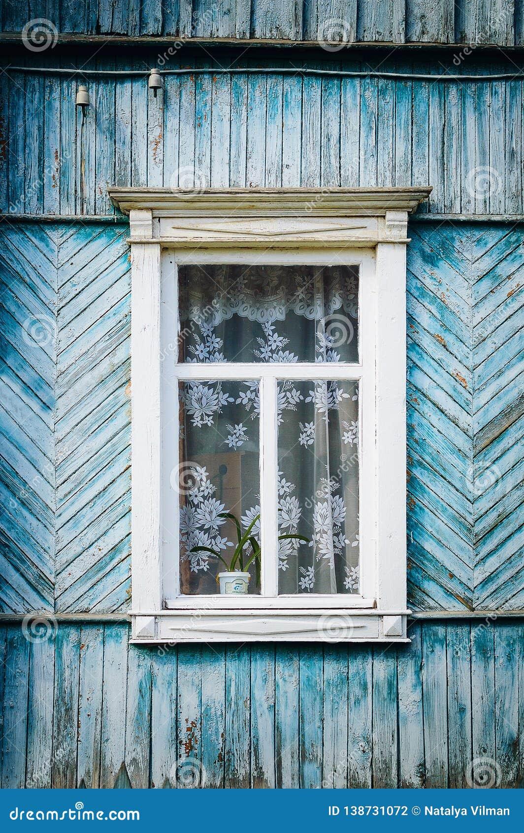 与铰链和被雕刻的快门的老被风化的木窗口 减速火箭