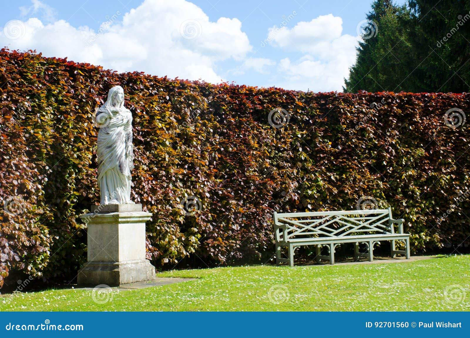 与长凳的雕象在英国国家庭院里