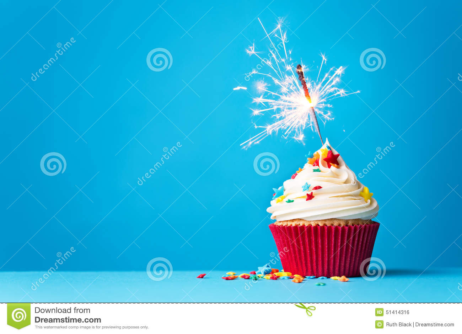与闪烁发光物的杯形蛋糕在蓝色