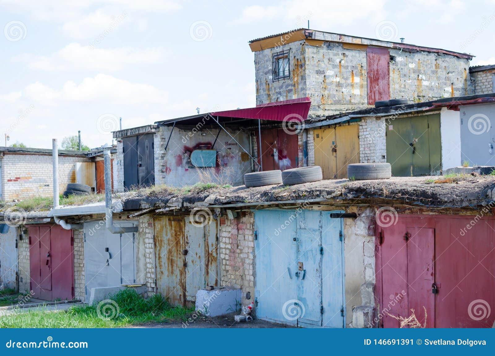 与闭合的生锈的门的老车库被堆积在彼此顶部