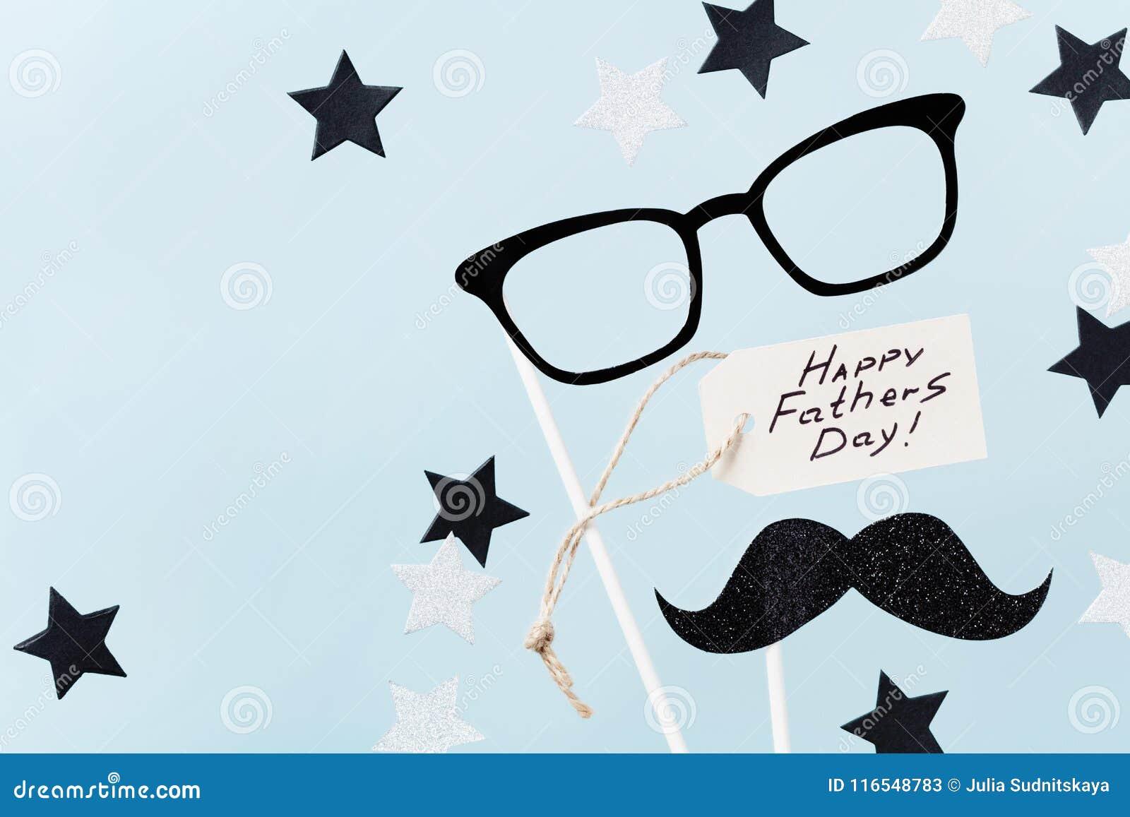 与问候标记、玻璃、滑稽的髭和星五彩纸屑的愉快的父亲节背景在台式视图 平的位置样式