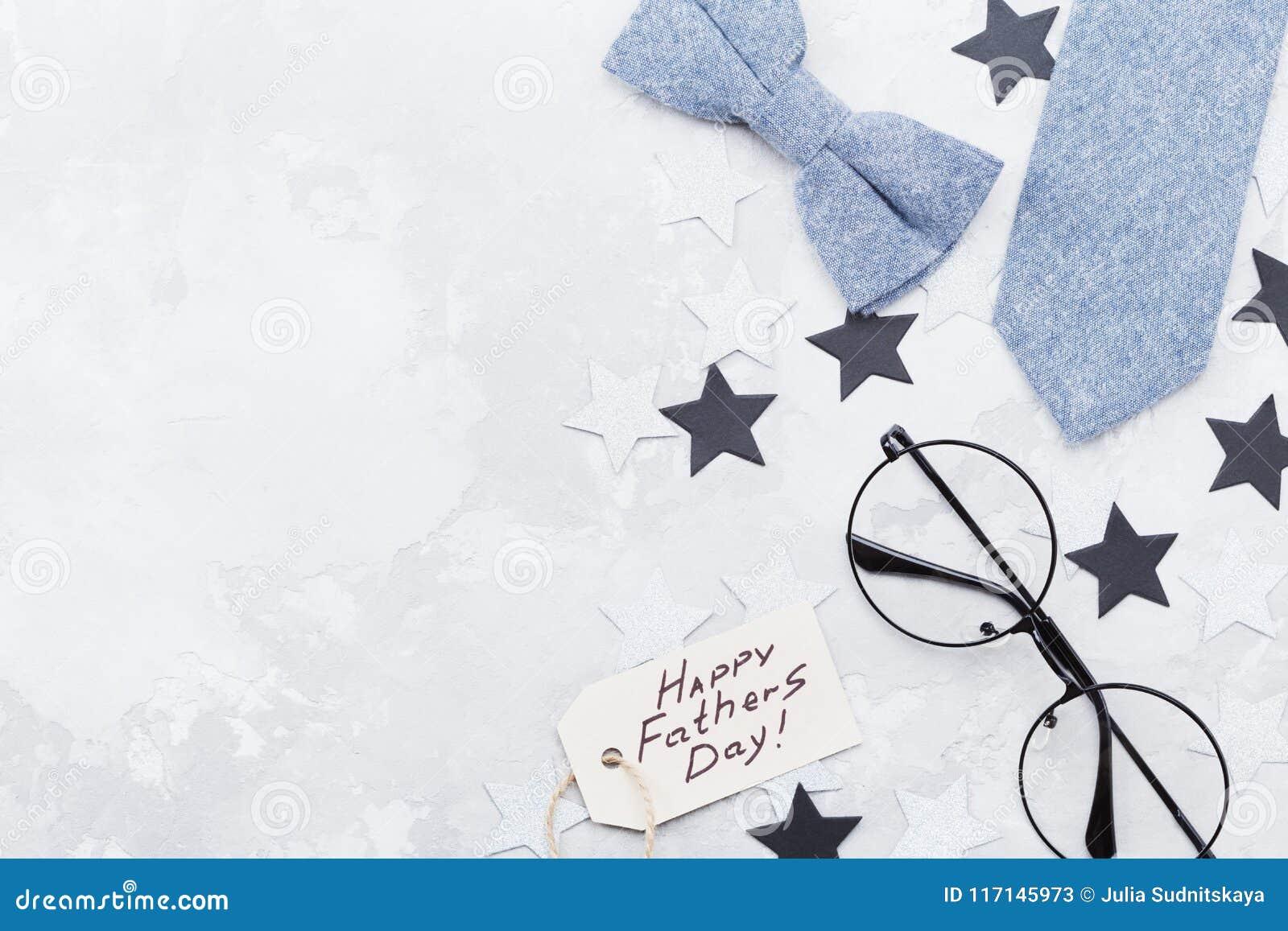 与问候标记、玻璃、领带、bowtie和星五彩纸屑的愉快的父亲节背景在台式视图 平的位置