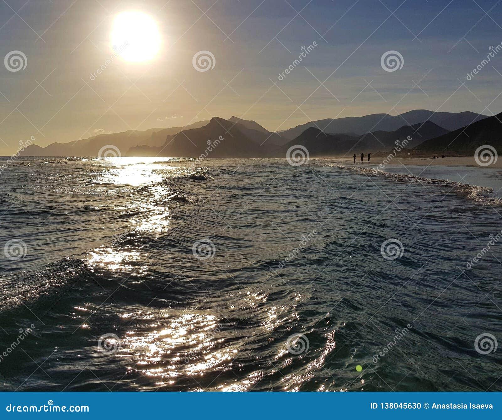 与阳光反射和山的不安定的海波浪