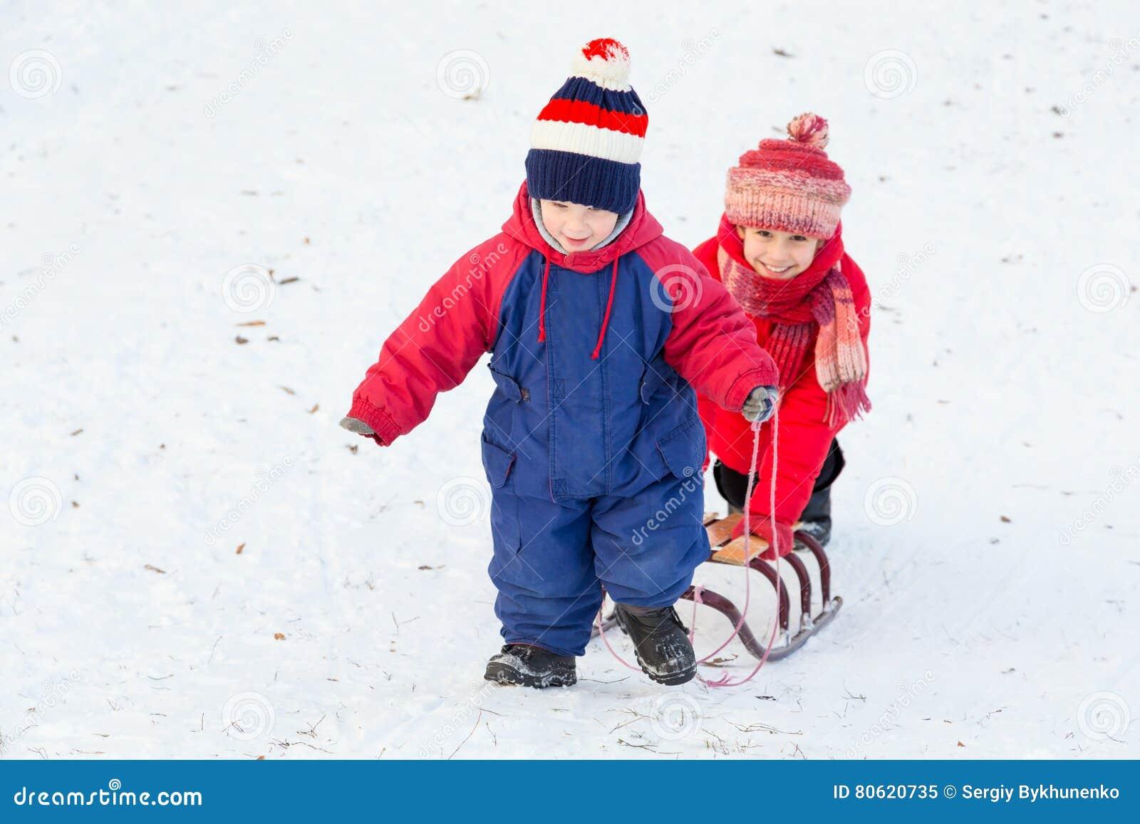 与雪撬的两个愉快的孩子走在雪的倾斜