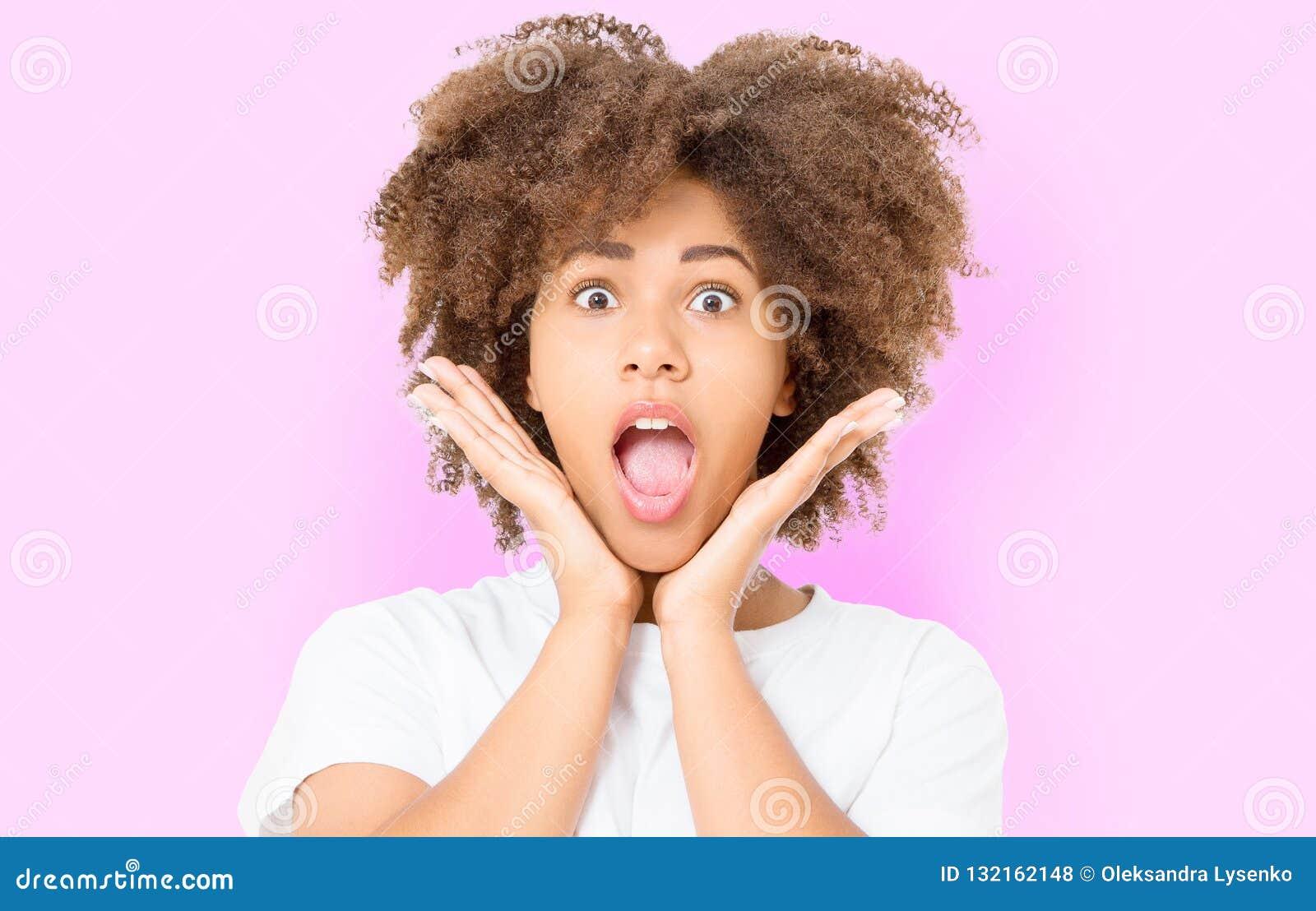 与非洲的卷发的愉快的惊奇的震惊激动的女孩面孔 在桃红色背景隔绝的年轻黑暗的皮肤妇女 非裔美国人