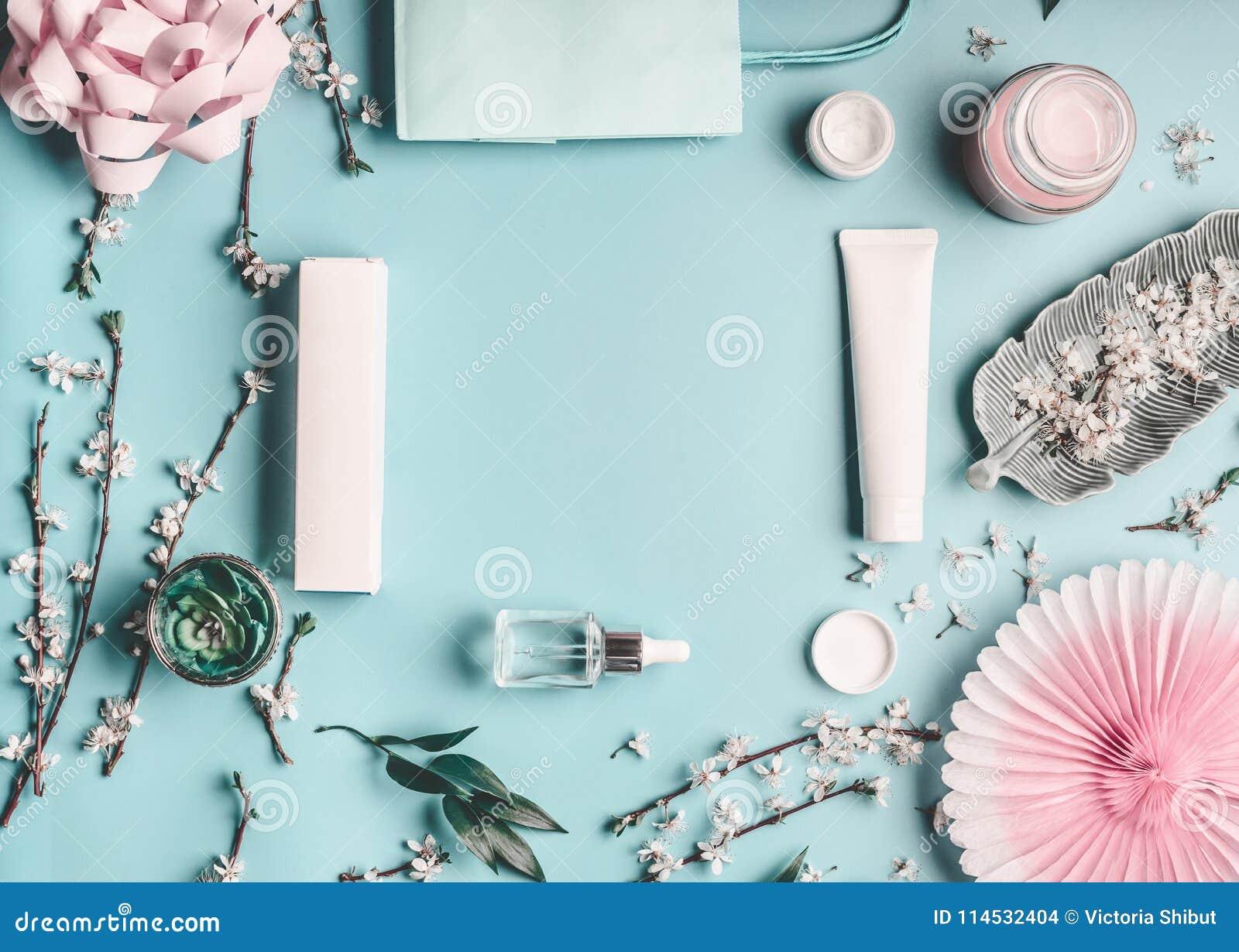 与面部化妆产品、购物袋和枝杈的秀丽概念有在淡色蓝色桌面上的樱花的