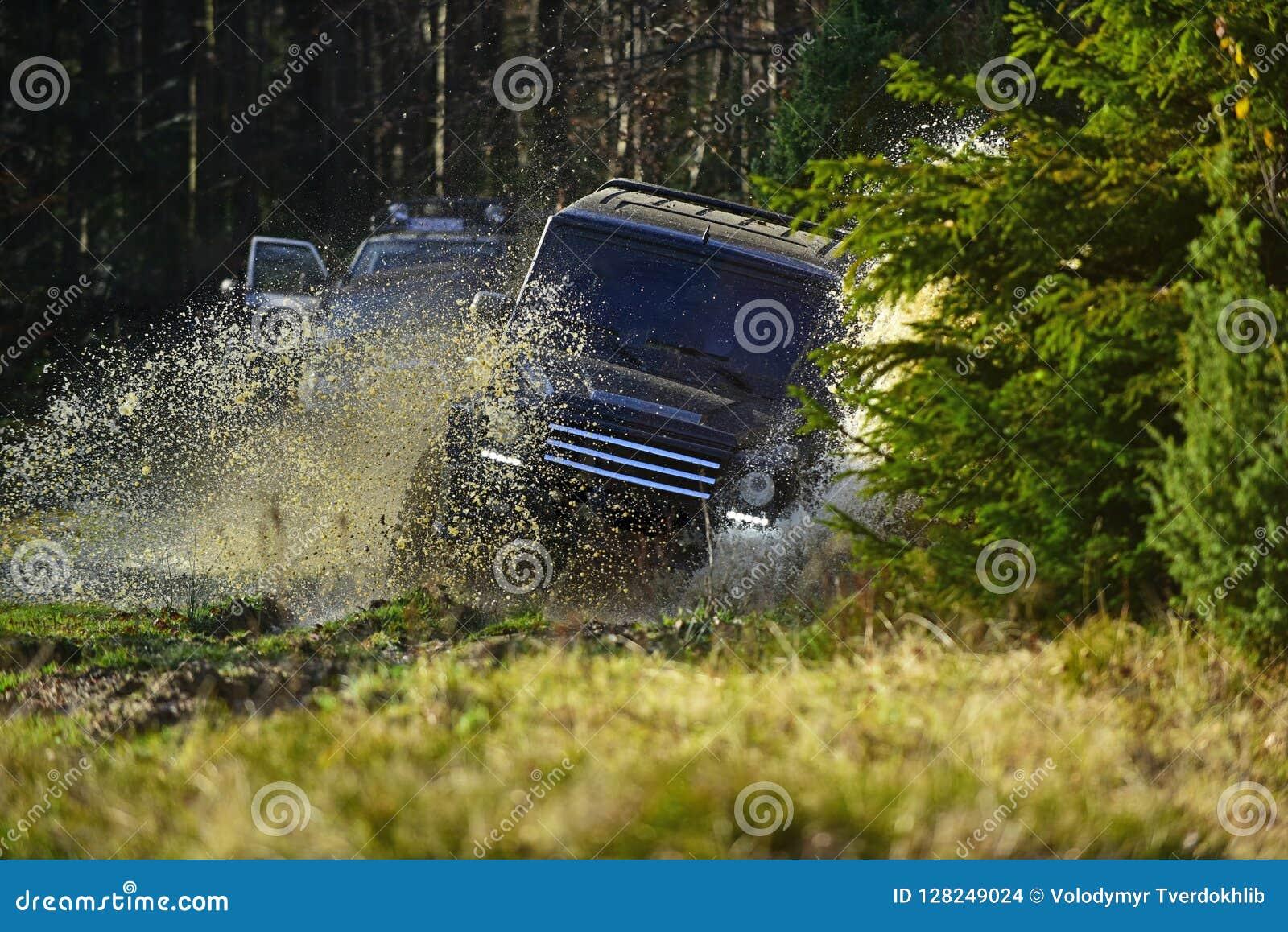 与飞溅的越野车或SUV横穿水坑 召集,竞争和四轮驱动的概念 马达