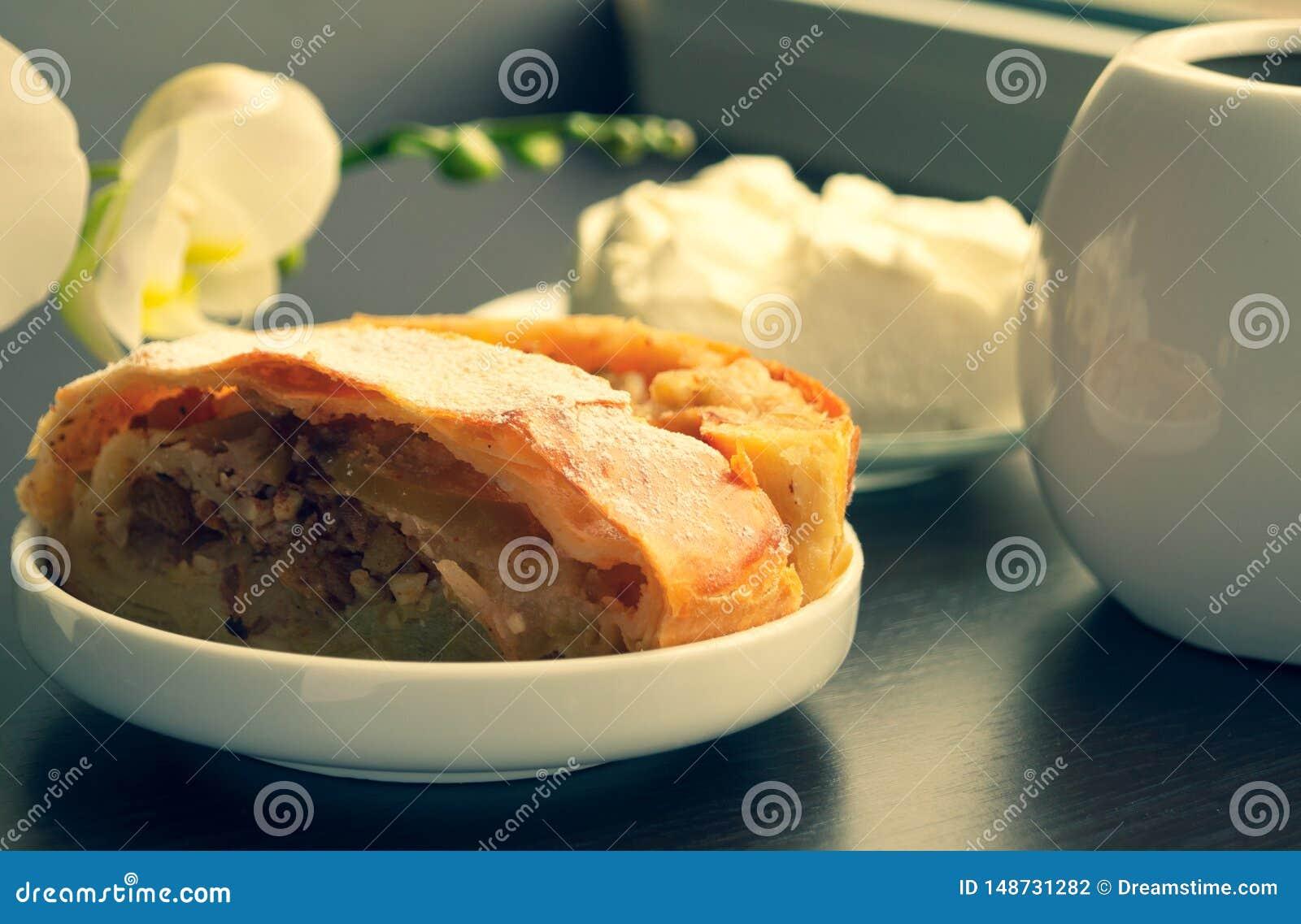 与香草冰淇淋和咖啡的苹果果馅奶酪卷在用archeid装饰的黑暗的背景在清早