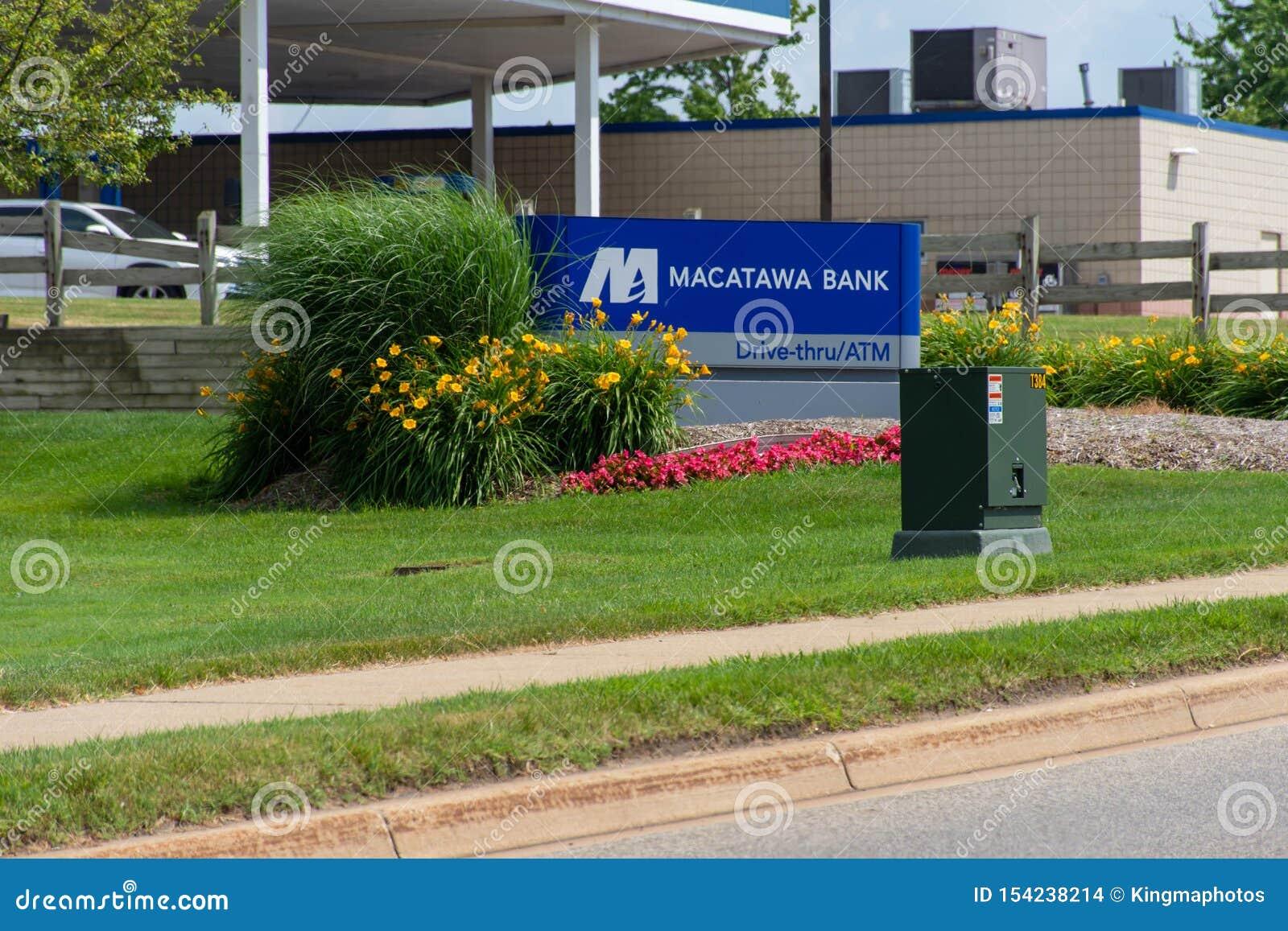 与驱动,通过atm和花的蓝色Macatawa银行标志在绿草和天空蔚蓝
