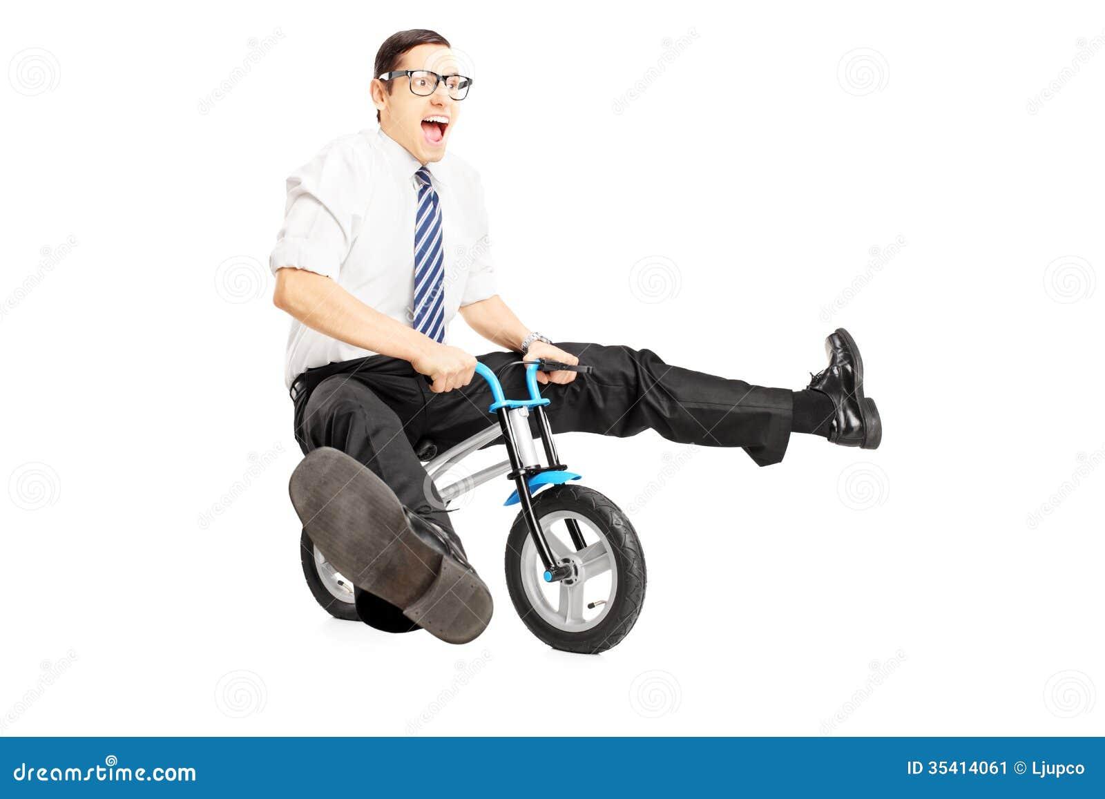 与骑一辆小自行车的领带的讨厌的年轻男性