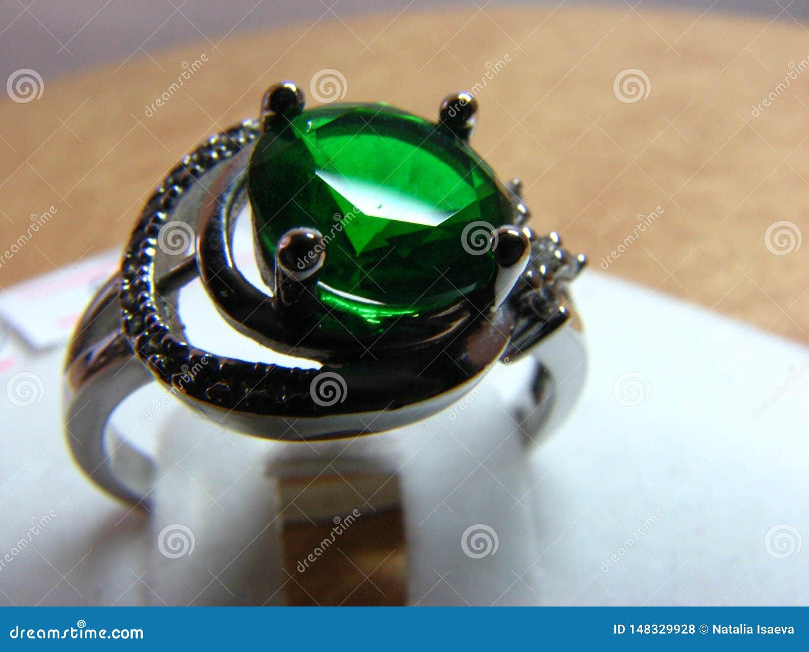 与鲜绿色石头的银色圆环