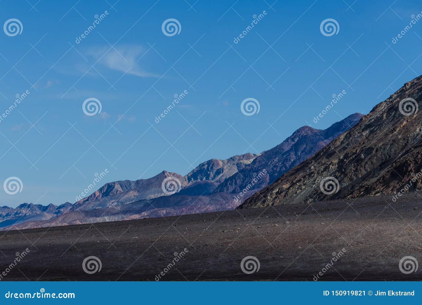 与黑暗的火山的地球的贫瘠沙漠风景和后退入距离的坚固性山脉