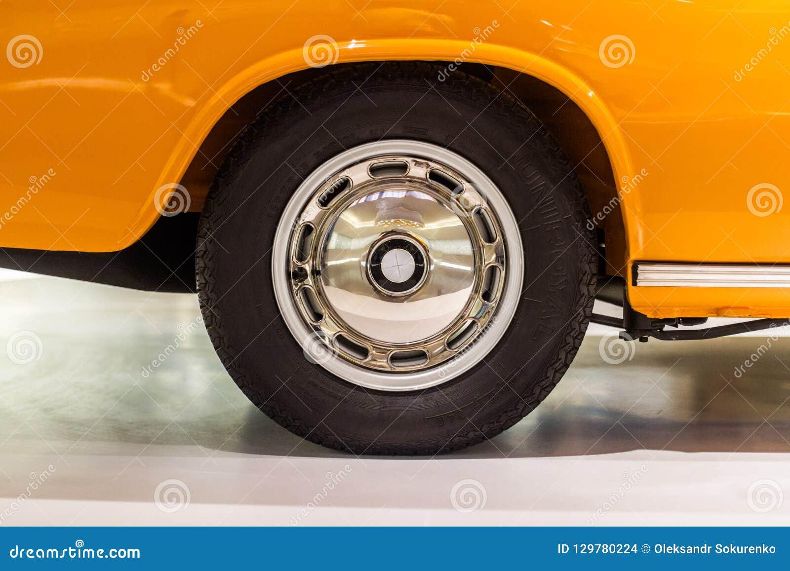 与黑葡萄酒轮子的优美的汽车外缘在橙色汽车