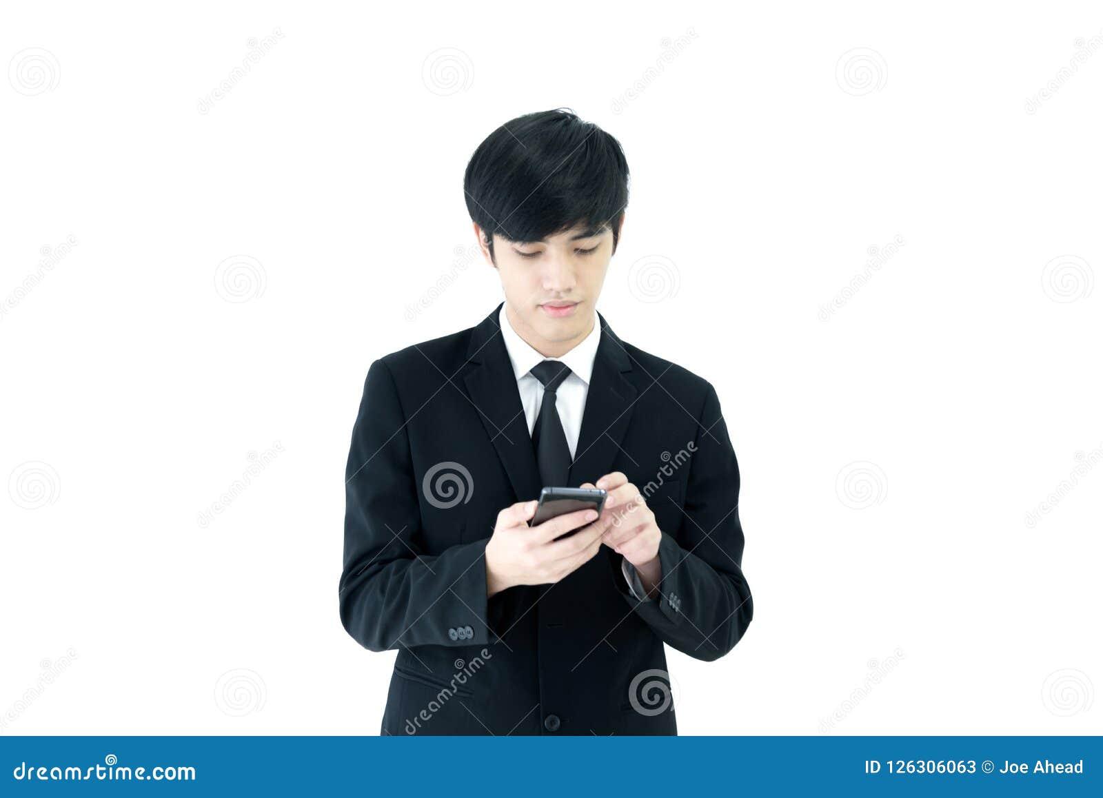 与黑衣服和黑领带的亚洲商人有使用在白色背景隔绝的电话