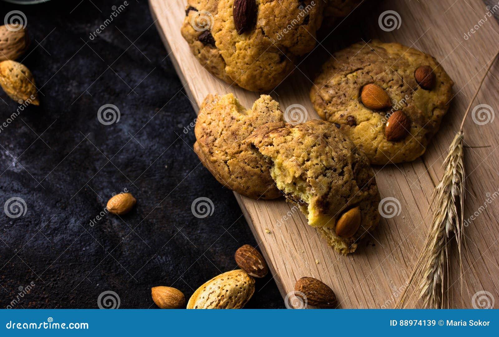 与黑人的美国一种油脂含量较高的酥饼和一个水罐牛奶和杏仁 黑暗的难看的东西背景 神秘的光