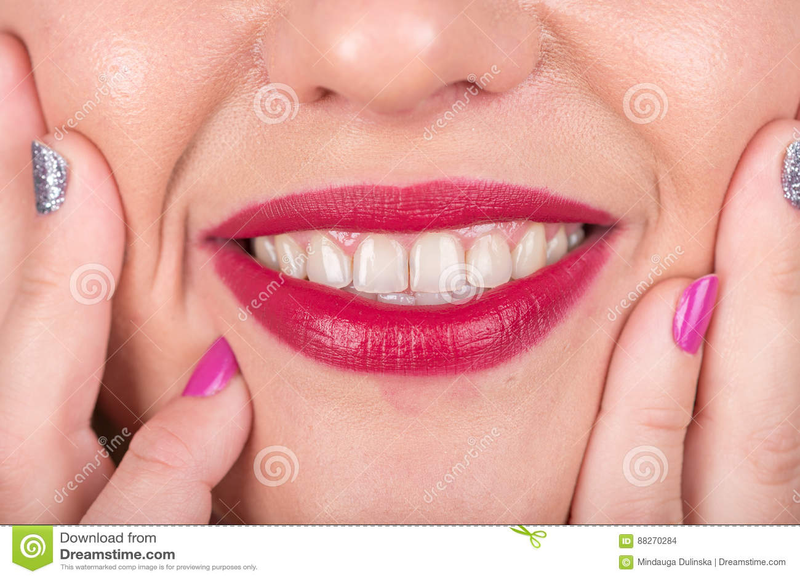 与嘴唇和手指的愉快的妇女面孔有波兰钉子的 演播室照片写真