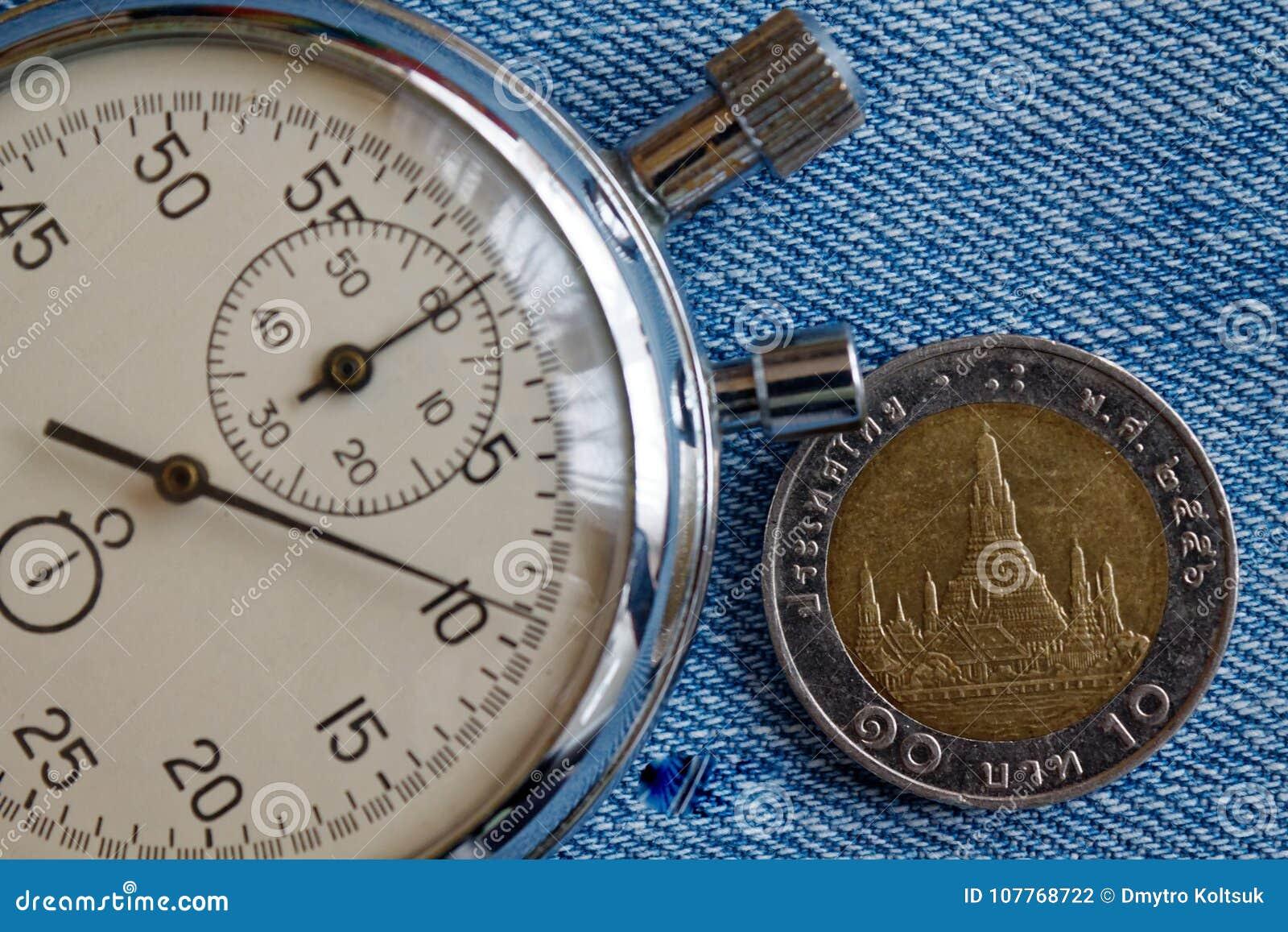与10在蓝色被佩带的牛仔裤背景-企业背景的泰铢(后部)和秒表的衡量单位的泰国硬币