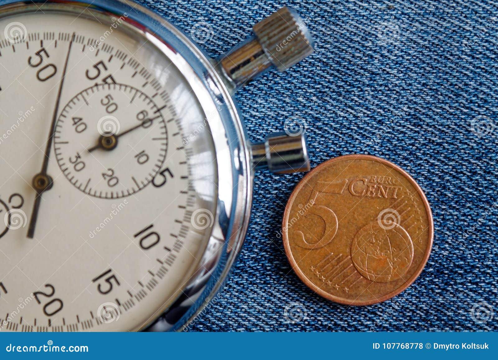 与5块欧分和秒表的衡量单位的欧洲硬币在破旧的蓝色牛仔布背景-企业背景