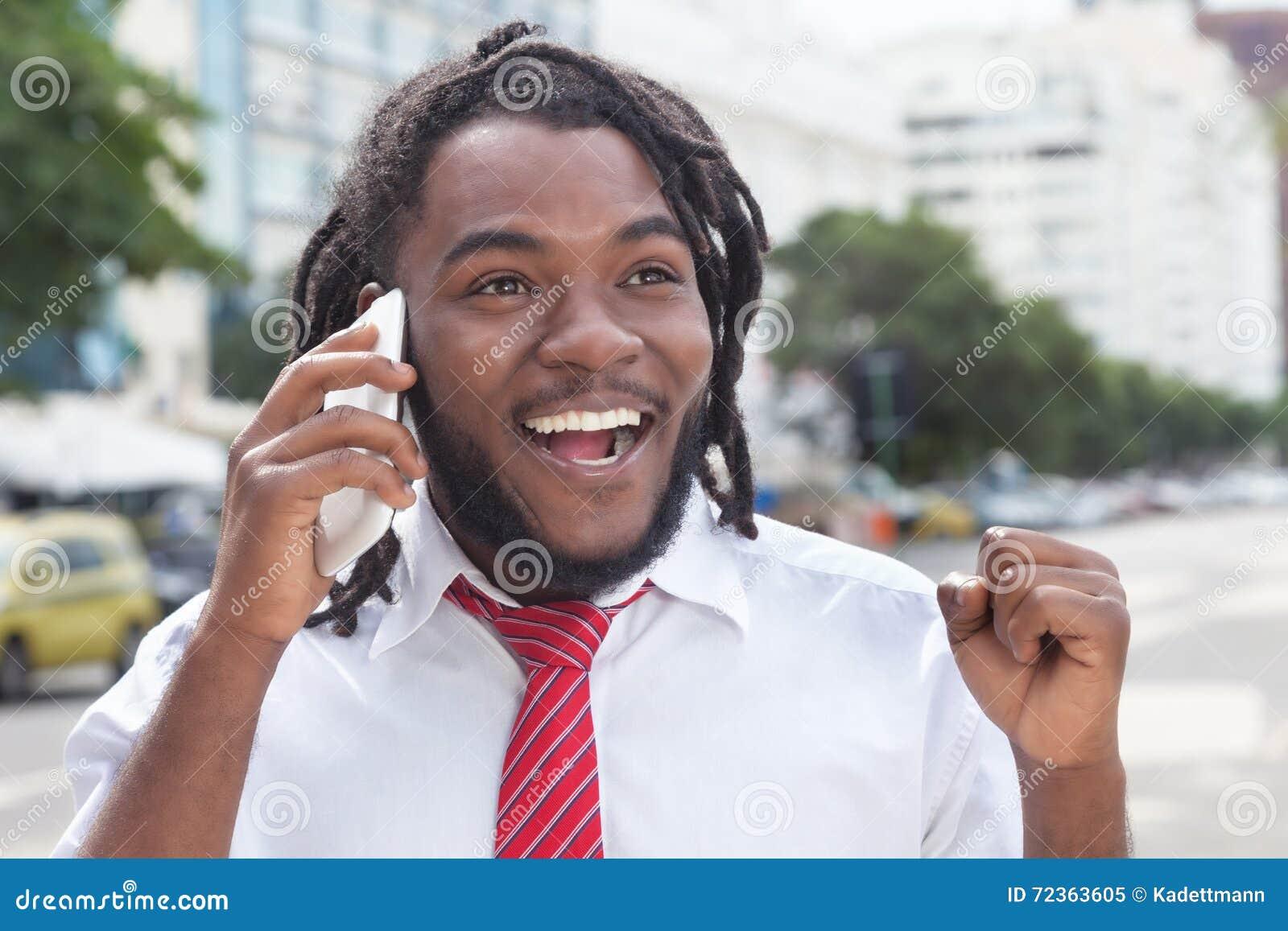 与dreadlocks的愉快的非裔美国人的商人在电话