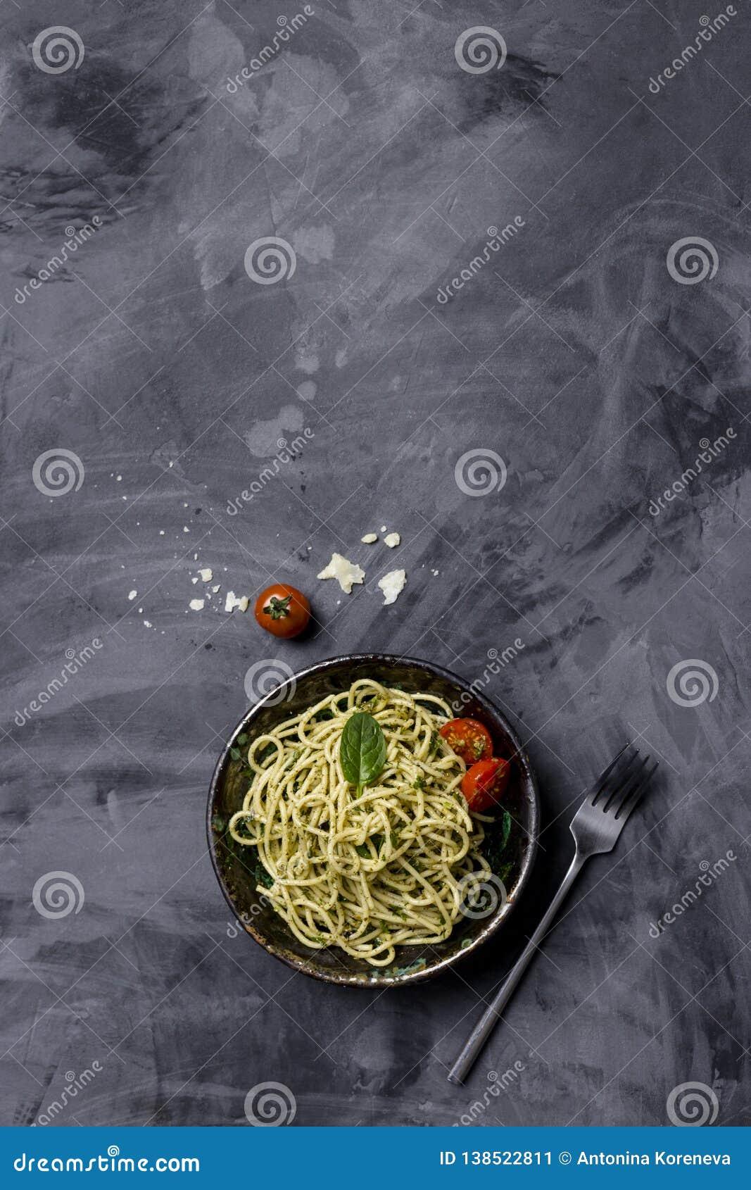 与pesto和西红柿的面团在黑背景,顶视图
