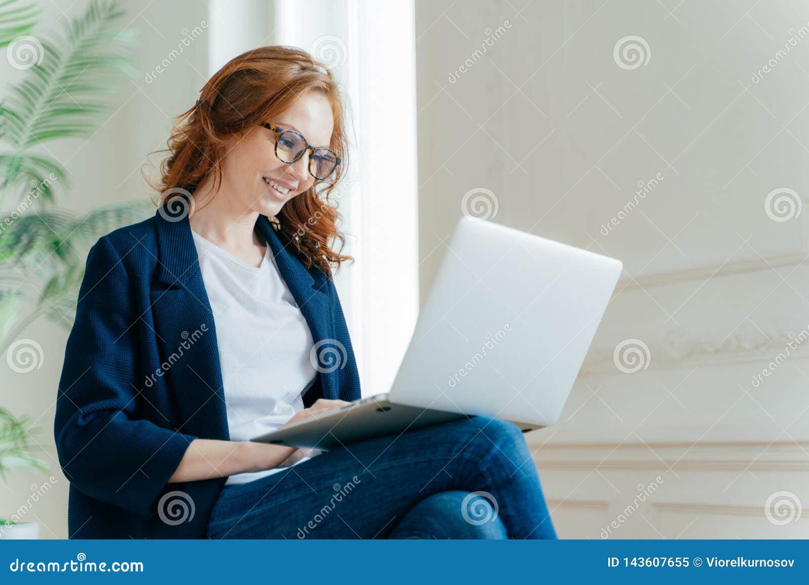 专业女性雇主喜欢工作过程,坐有膝上型计算机设备的盘的腿,聊天网上,有正面神色,有