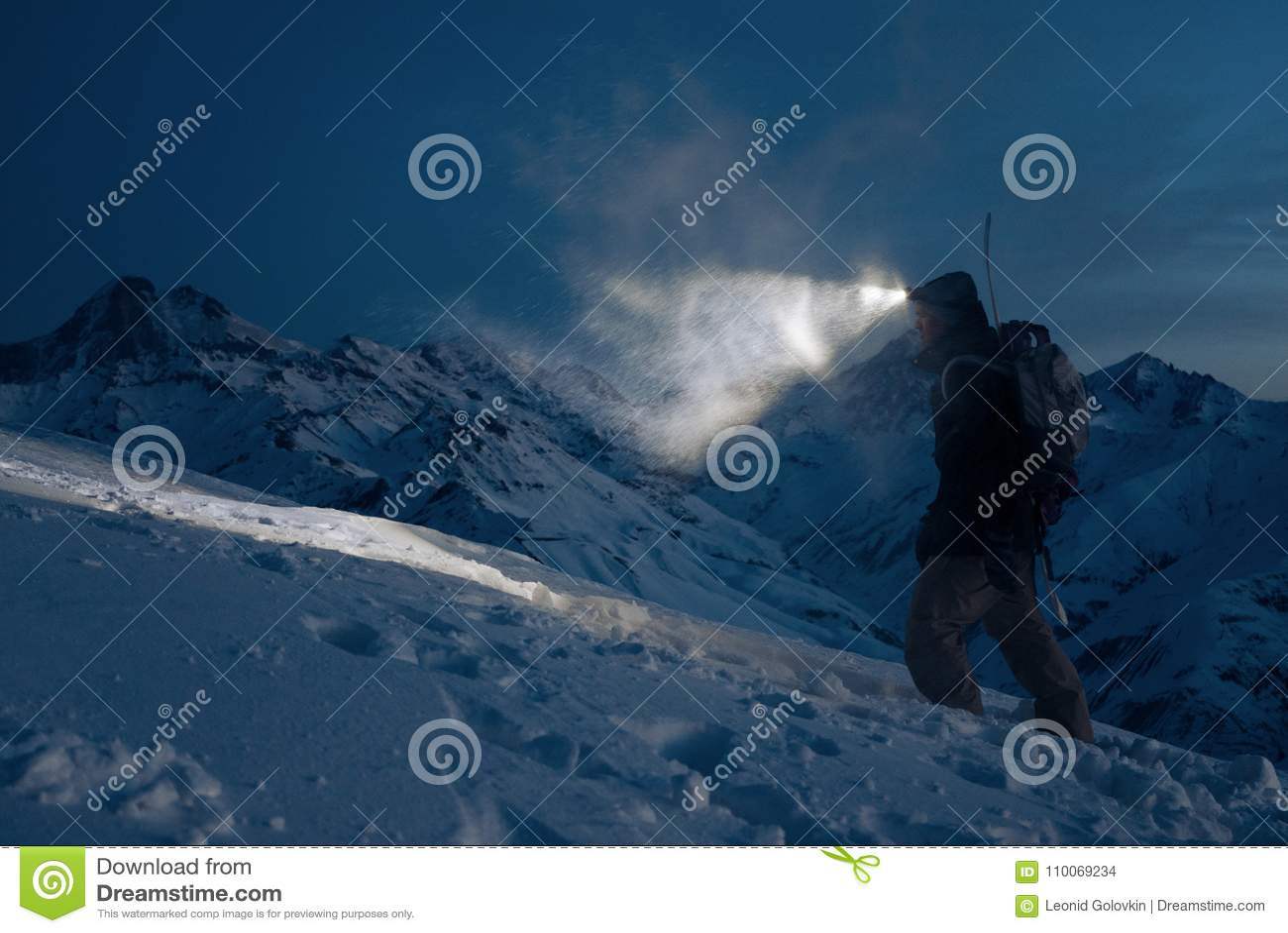 专业expeditor做在多雪的山的攀登在夜和光里与前灯的方式 佩带的滑雪穿戴,背包和