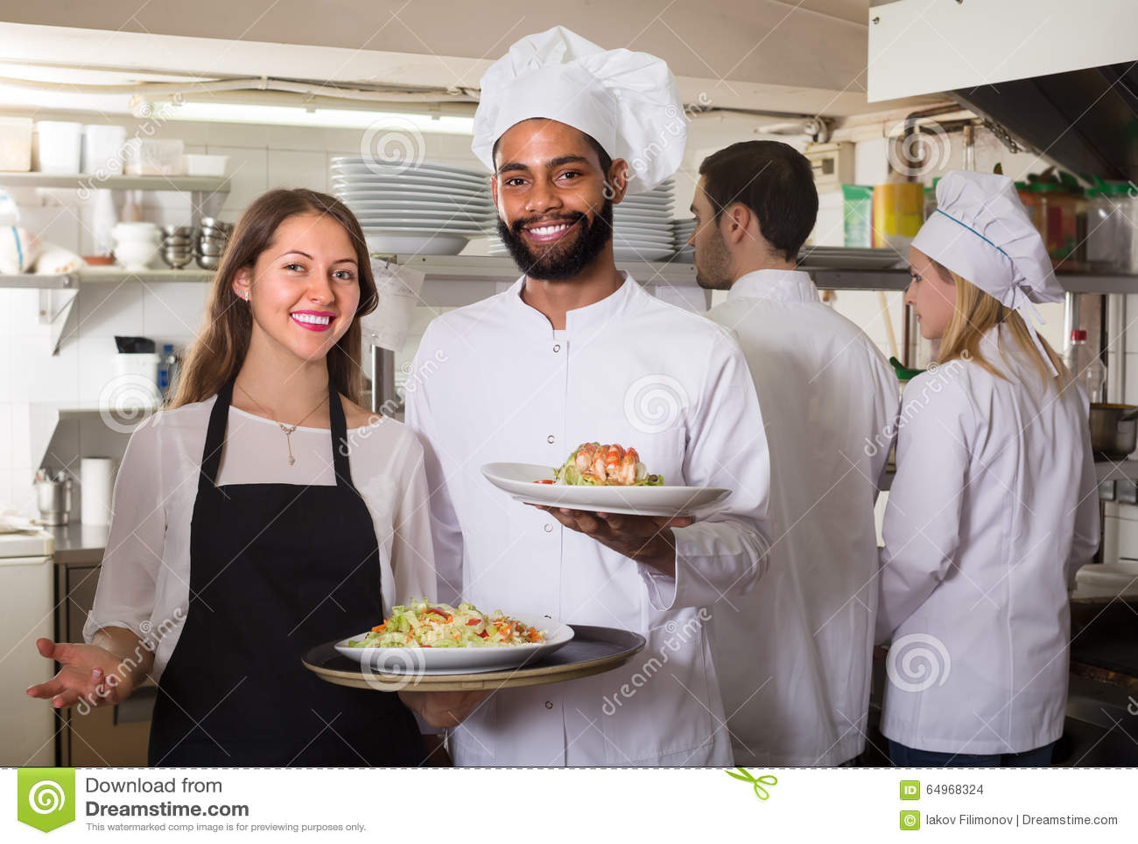 专家女服务员和乘员组在餐馆烹调摆在