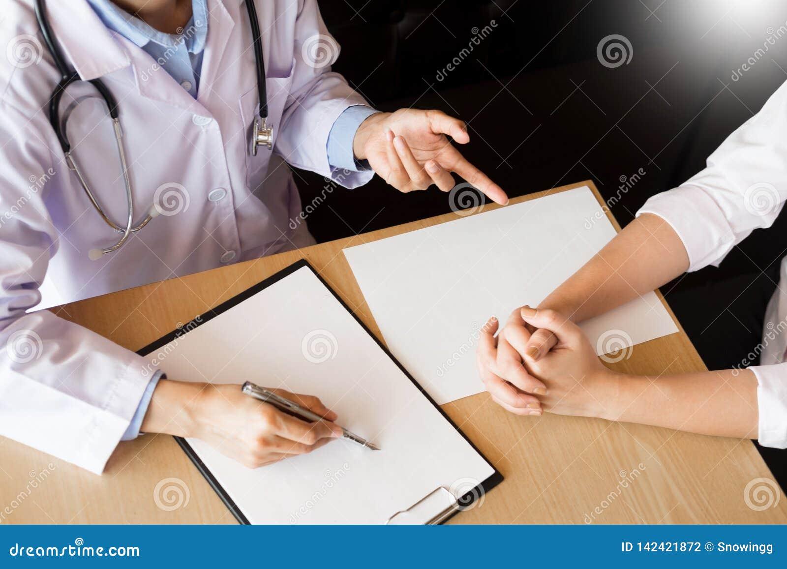 专心地听一位男性医生的患者解释耐心症状或问问题,他们一起谈论文书工作