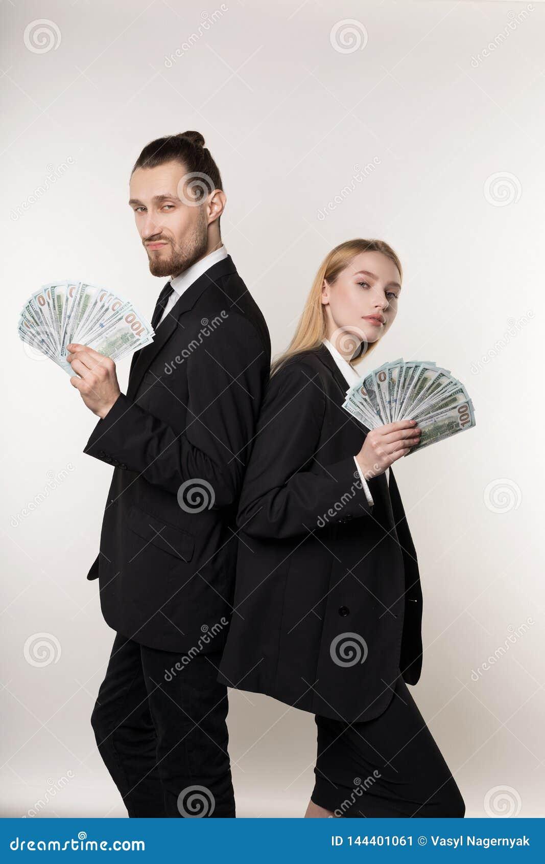 两个严肃的商务伙伴英俊的有胡子的紧接站立与金钱的人和美丽的白肤金发的女孩在手上
