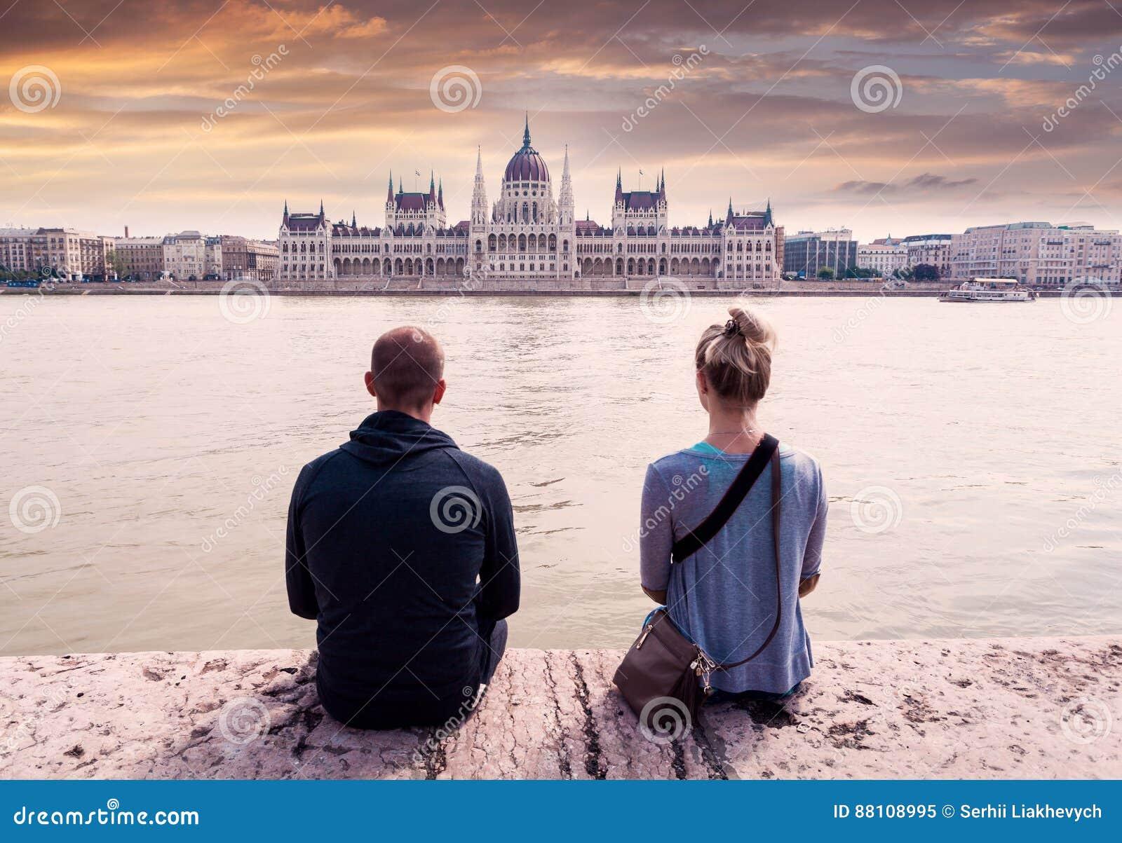 两个人坐江边并且享受观点的议会在布达佩斯,匈牙利