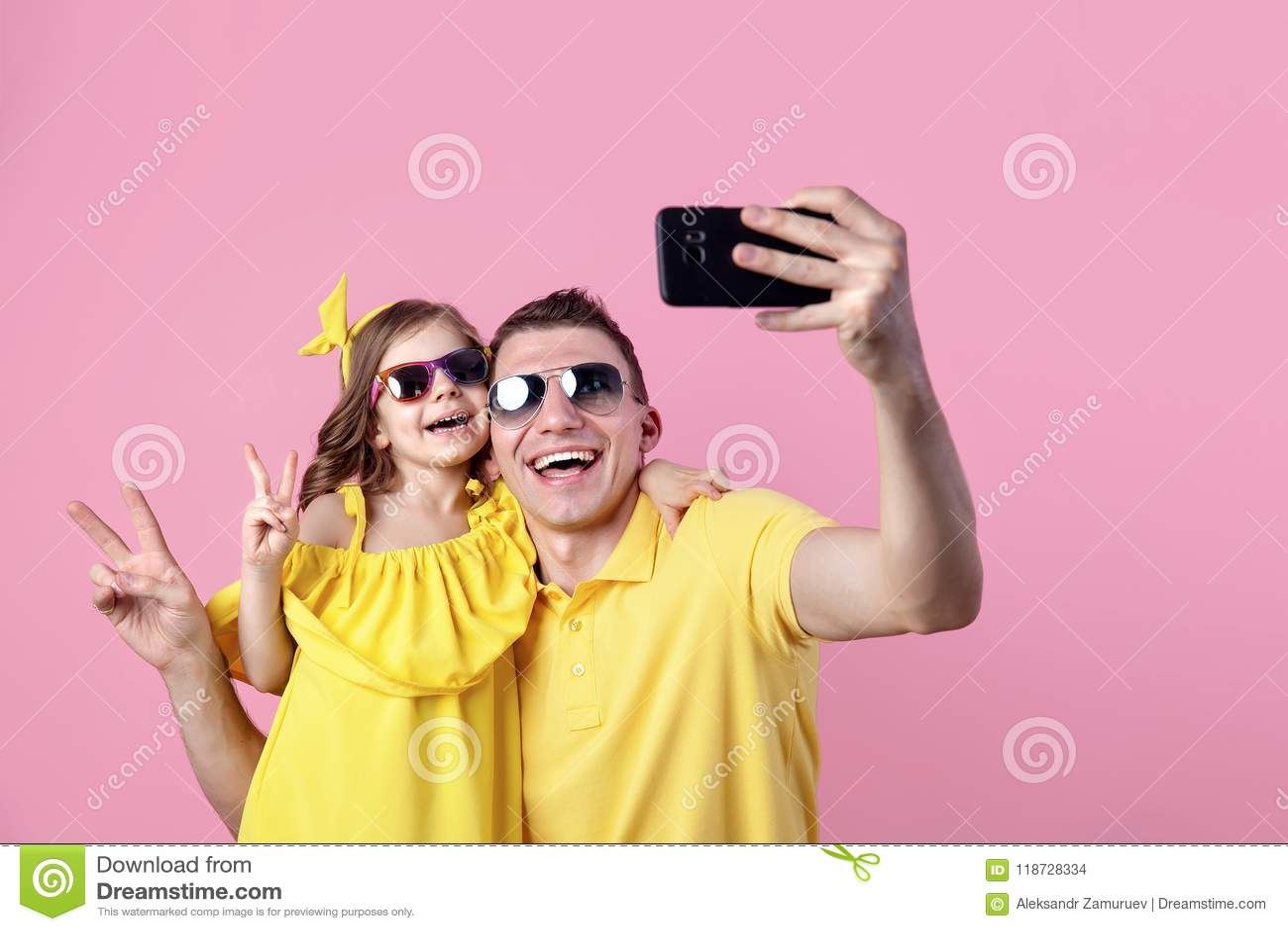 两个人愉快的家庭画象  做与智能手机的爸爸和小女儿selfie 水平的颜色