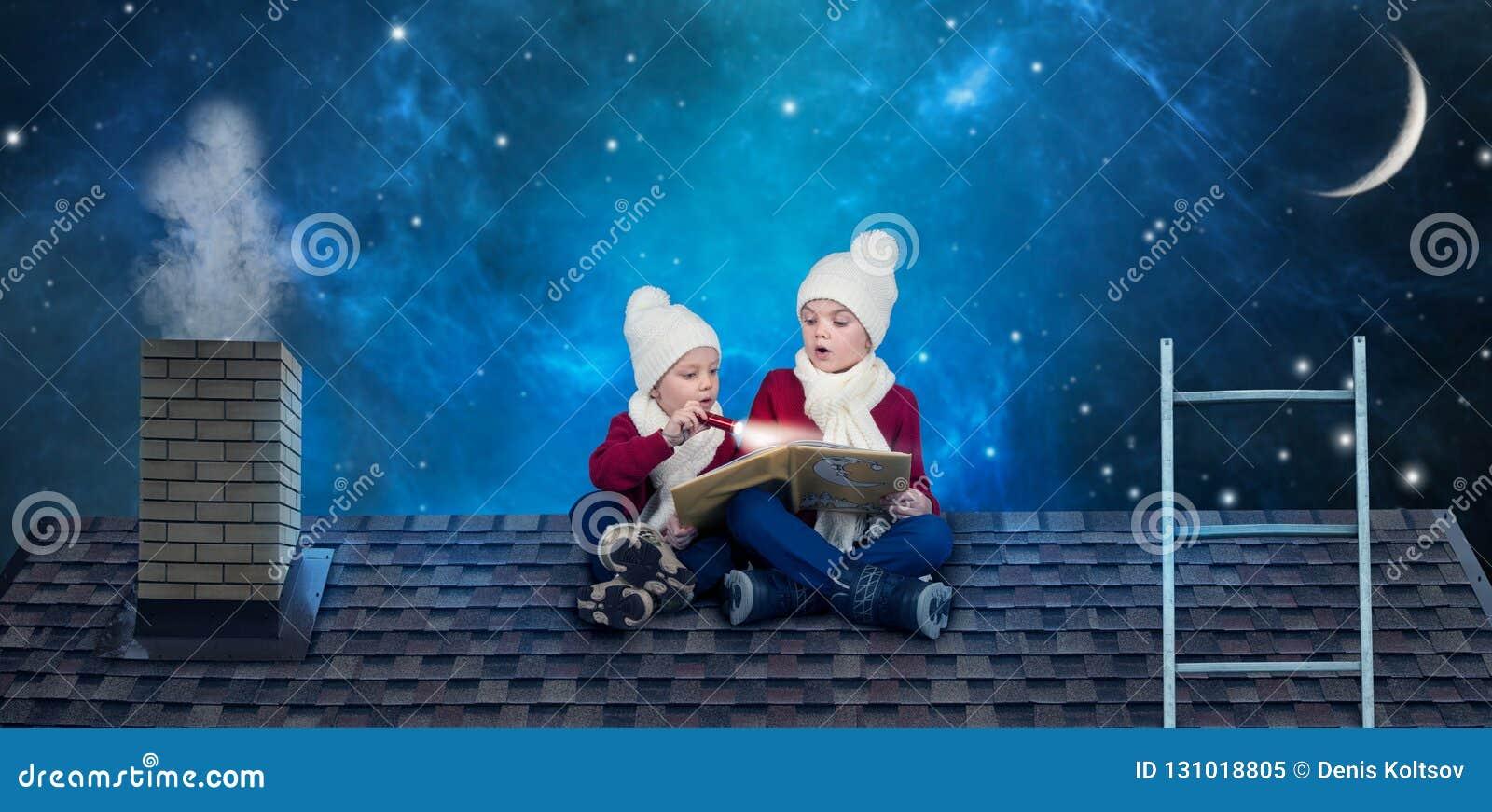 两个兄弟坐在屋顶的圣诞夜并且读与童话当中的一本书 预期圣诞节奇迹