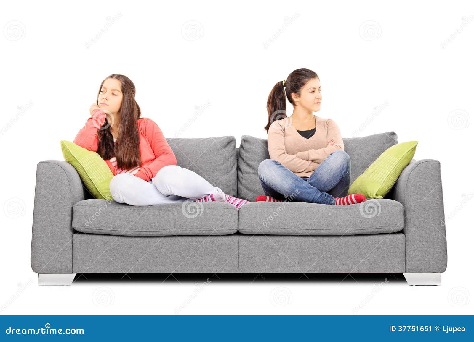 两个十几岁的女孩坐沙发不满对彼此