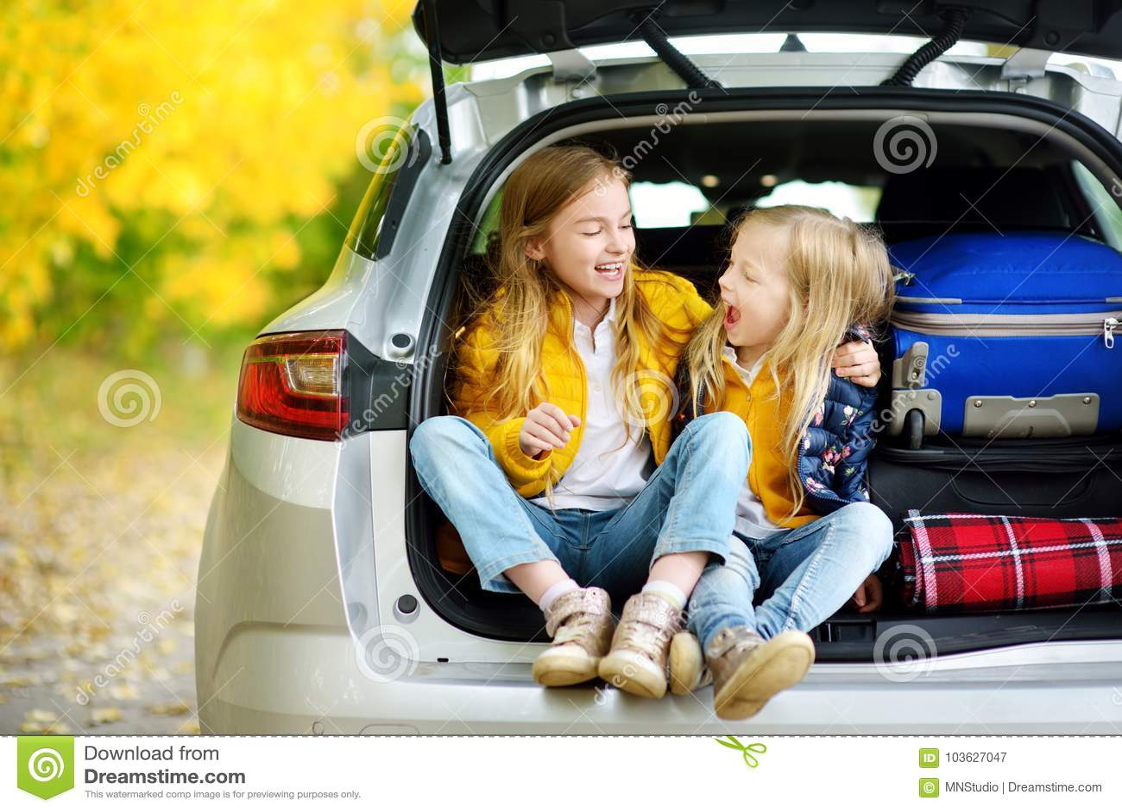 两个可爱的女孩在车厢在去前坐与他们的父母的假期 今后看为旅行o的两个孩子